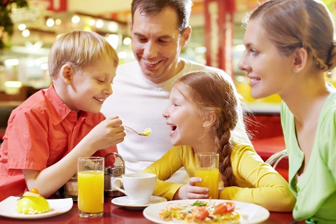 Family with two children sitting in cafe, the boy feeding his sister with spoon